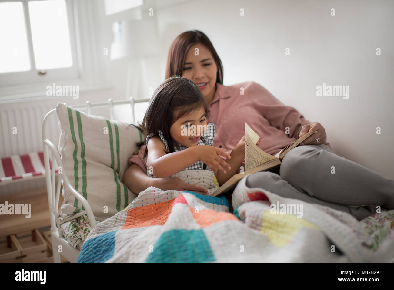 Girl turning page of a story book - Stock Image