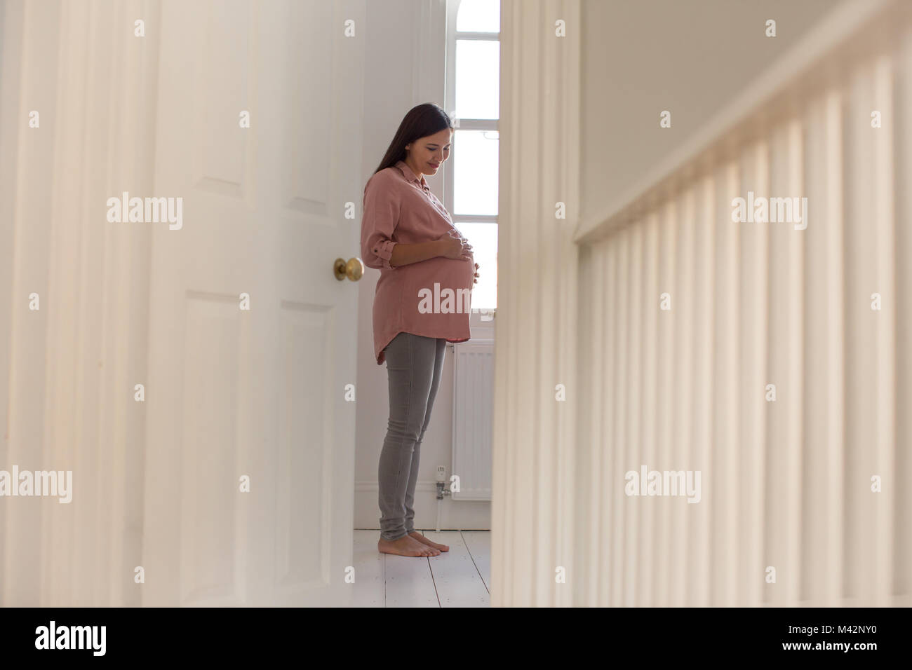 Pregnant woman standing in nursery room - Stock Image