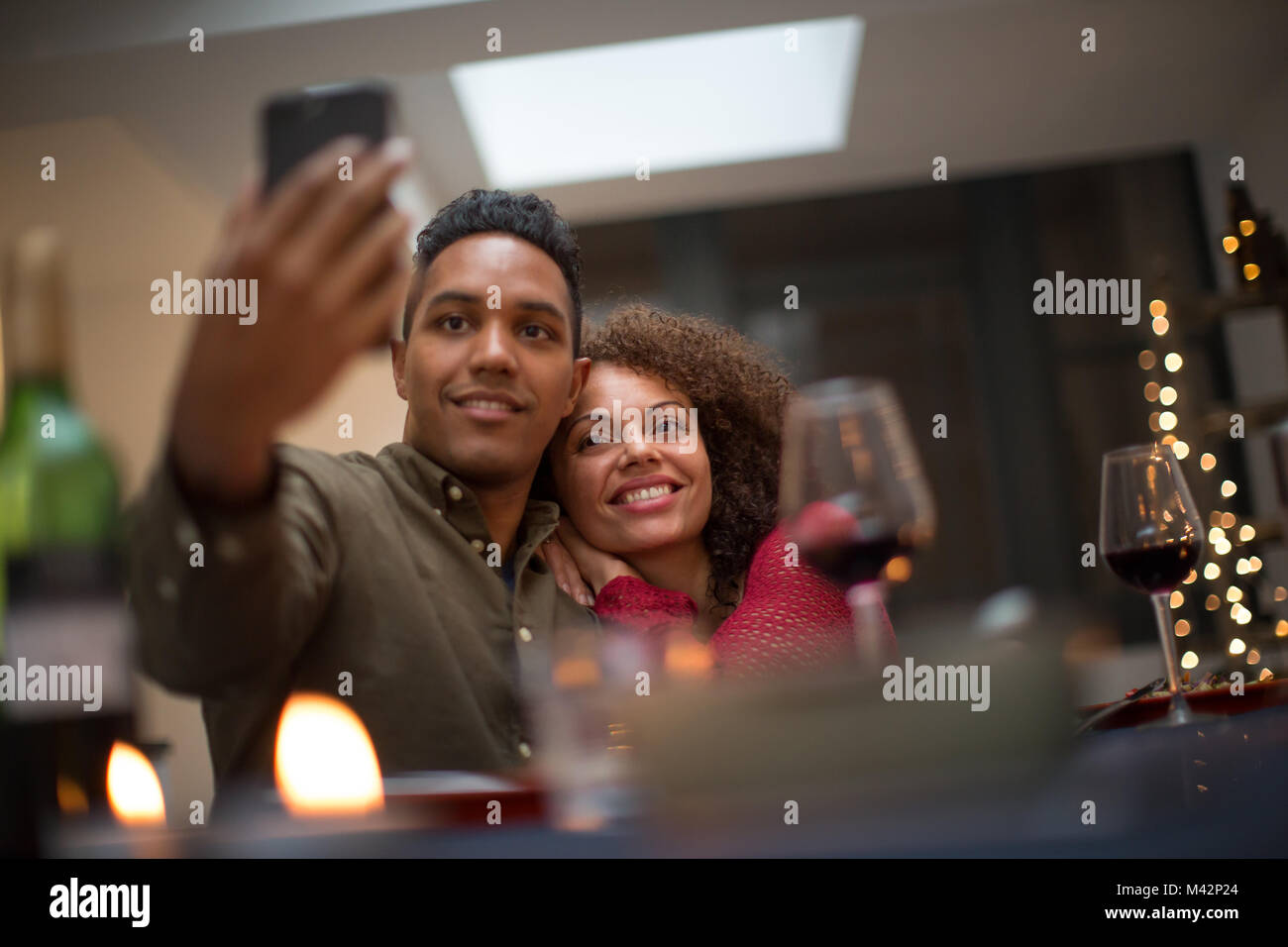 Couple taking a selfie at a celebration - Stock Image