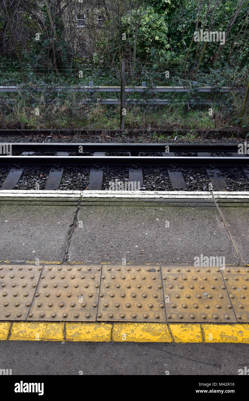 tactile slabs or coping stones on the edge of a platform at a mainline railway station with a yellow line safety Stock Photo
