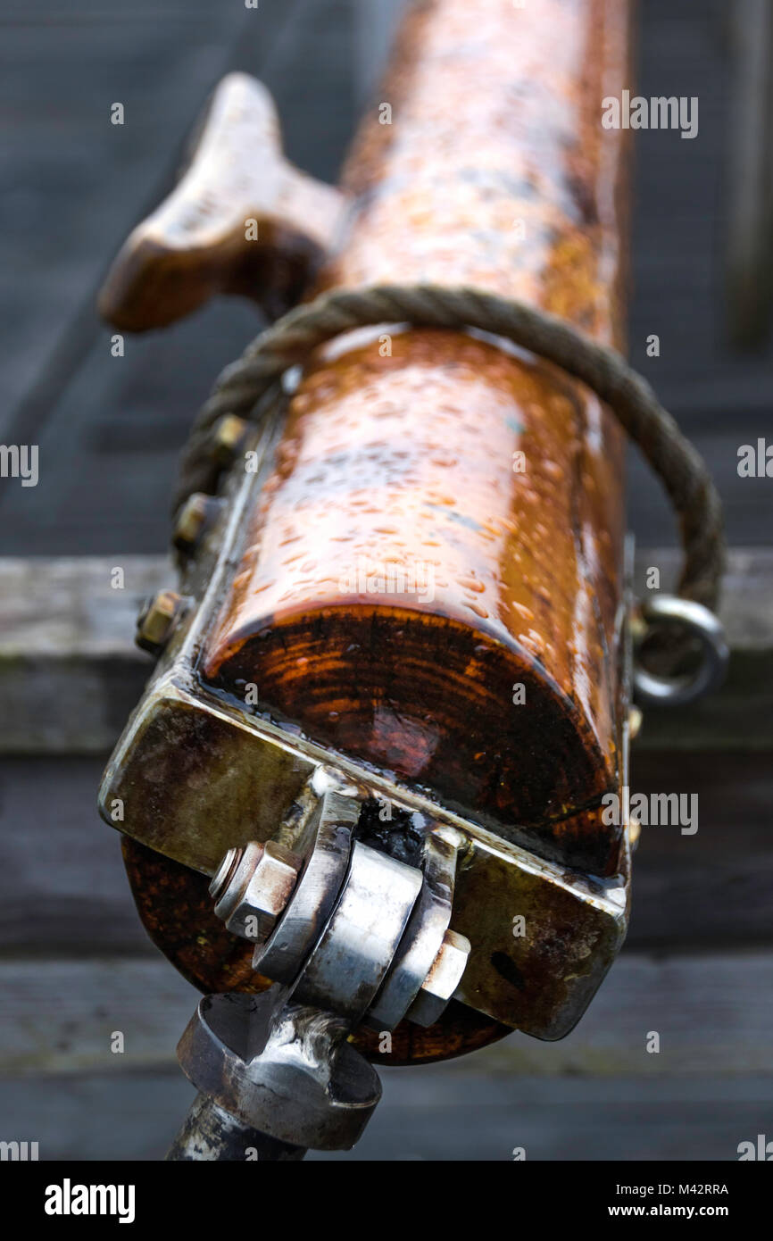up close photography of a wooden mast for a Sail boat, tied to the storage with a rope - Stock Image