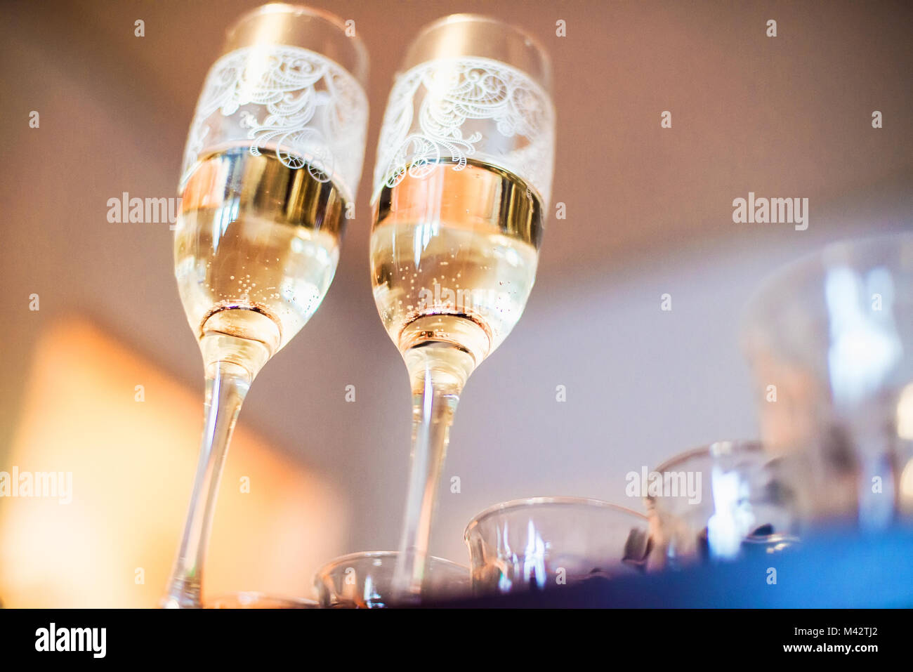 two glasses with champagne with wedding rings on the bottom photographed from the lower angle for a shallow depth - Stock Image