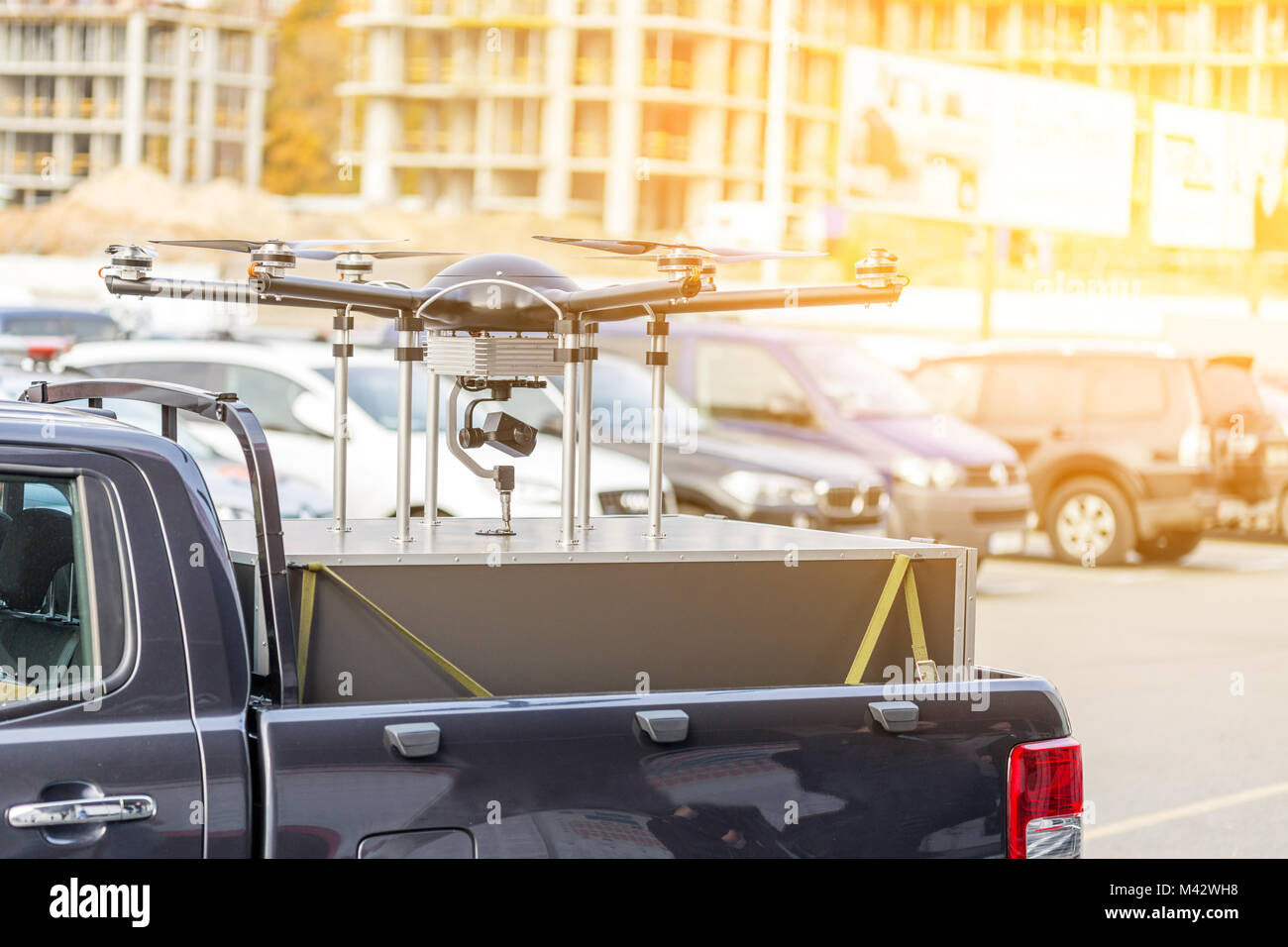 Big custom made drone over picup truck trunk.  Heavy UAV hexacopter with construction site on the background. Commercial - Stock Image