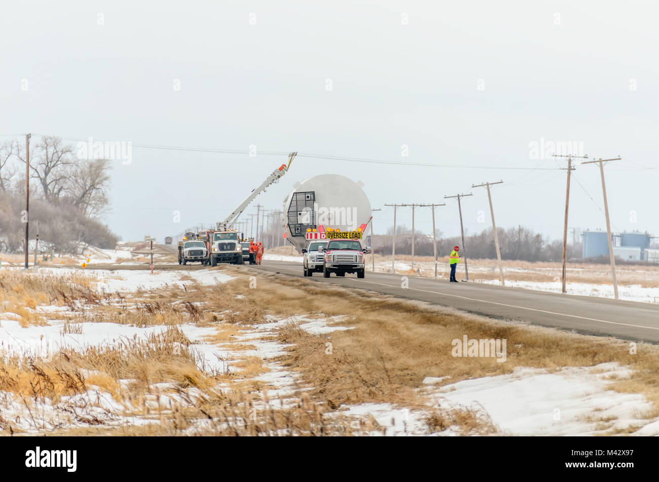 A team of road workers provides transportation of a huge oversized cargo in winter, by car under a power line - Stock Image
