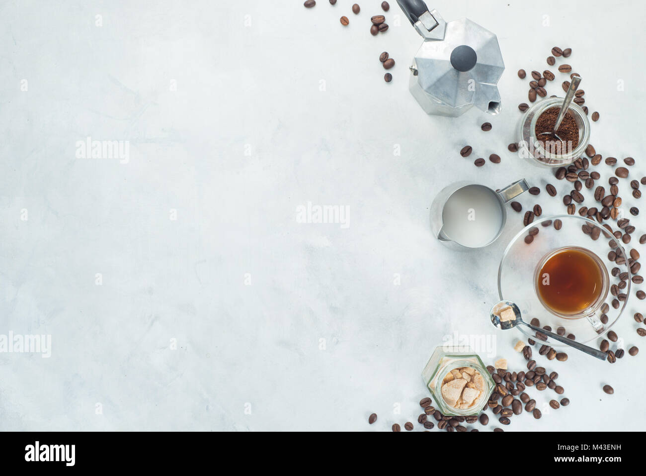 Brewing coffee in Moka pot concept. Glass espresso cup, milk jug, and sugar in high key flat lay on a white concrete - Stock Image