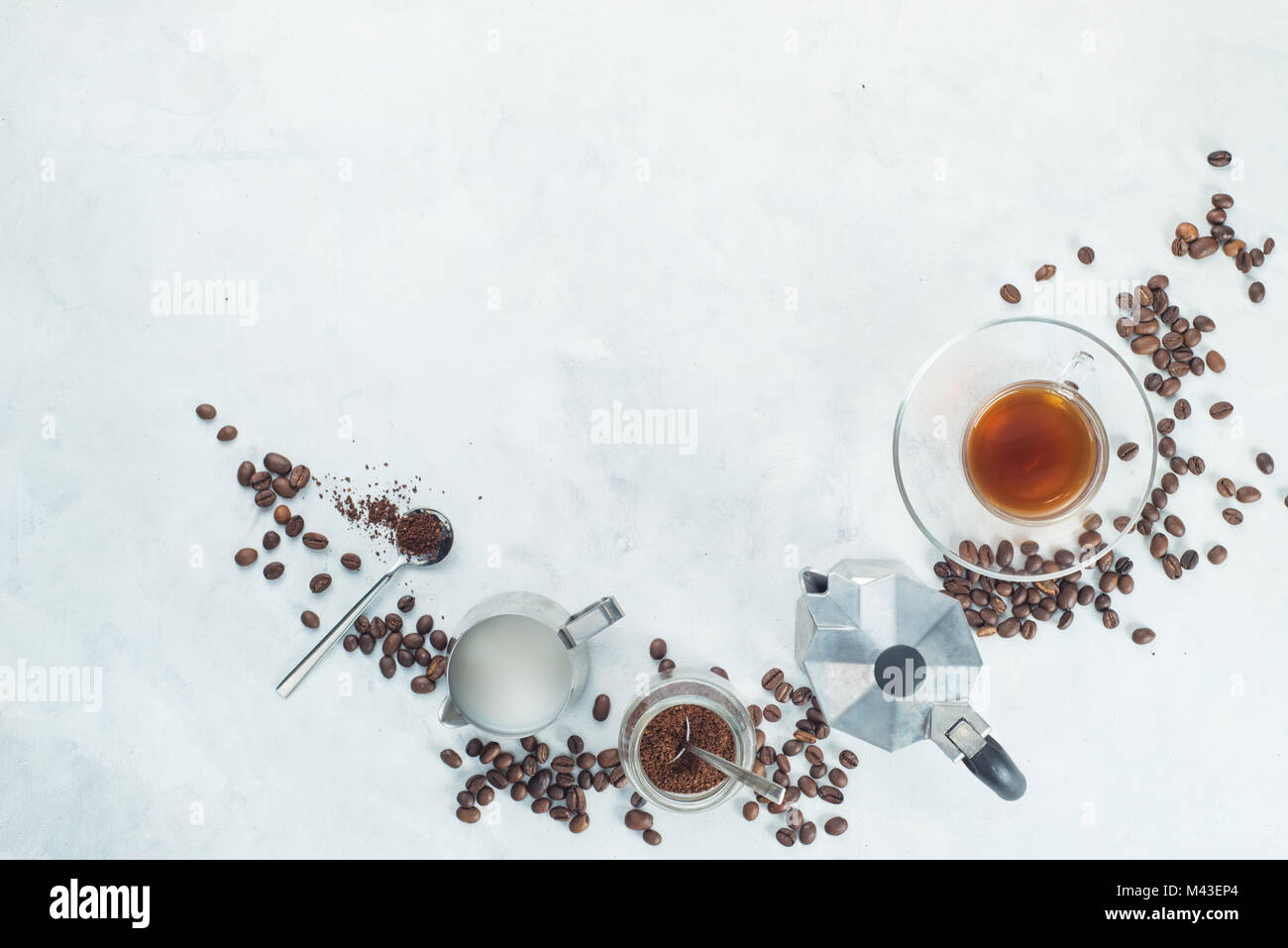 Header with brewing coffee ingredients. Moka pot, espresso cup, milk jug, ground coffee jar and coffee beans on - Stock Image