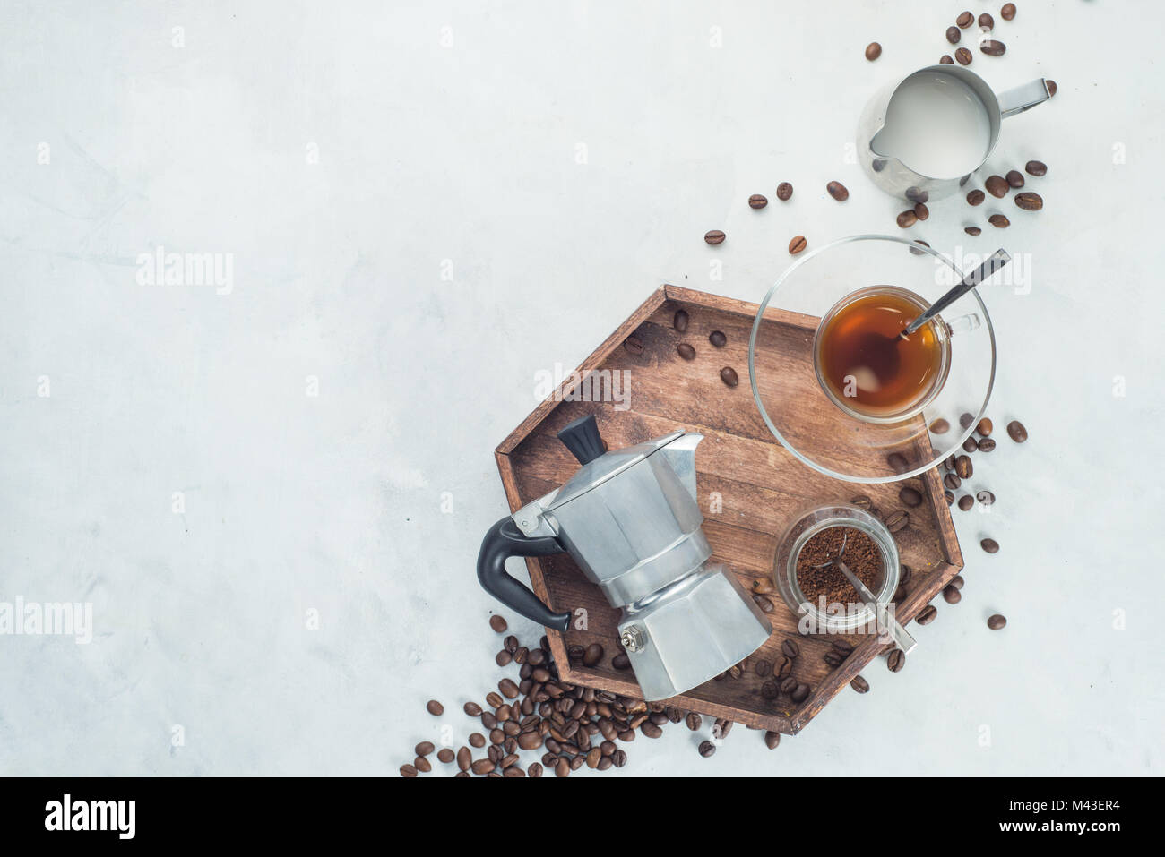 Wooden tray with Moka pot, espresso cup, ground coffee jar and coffee beans on a white concrete background with - Stock Image