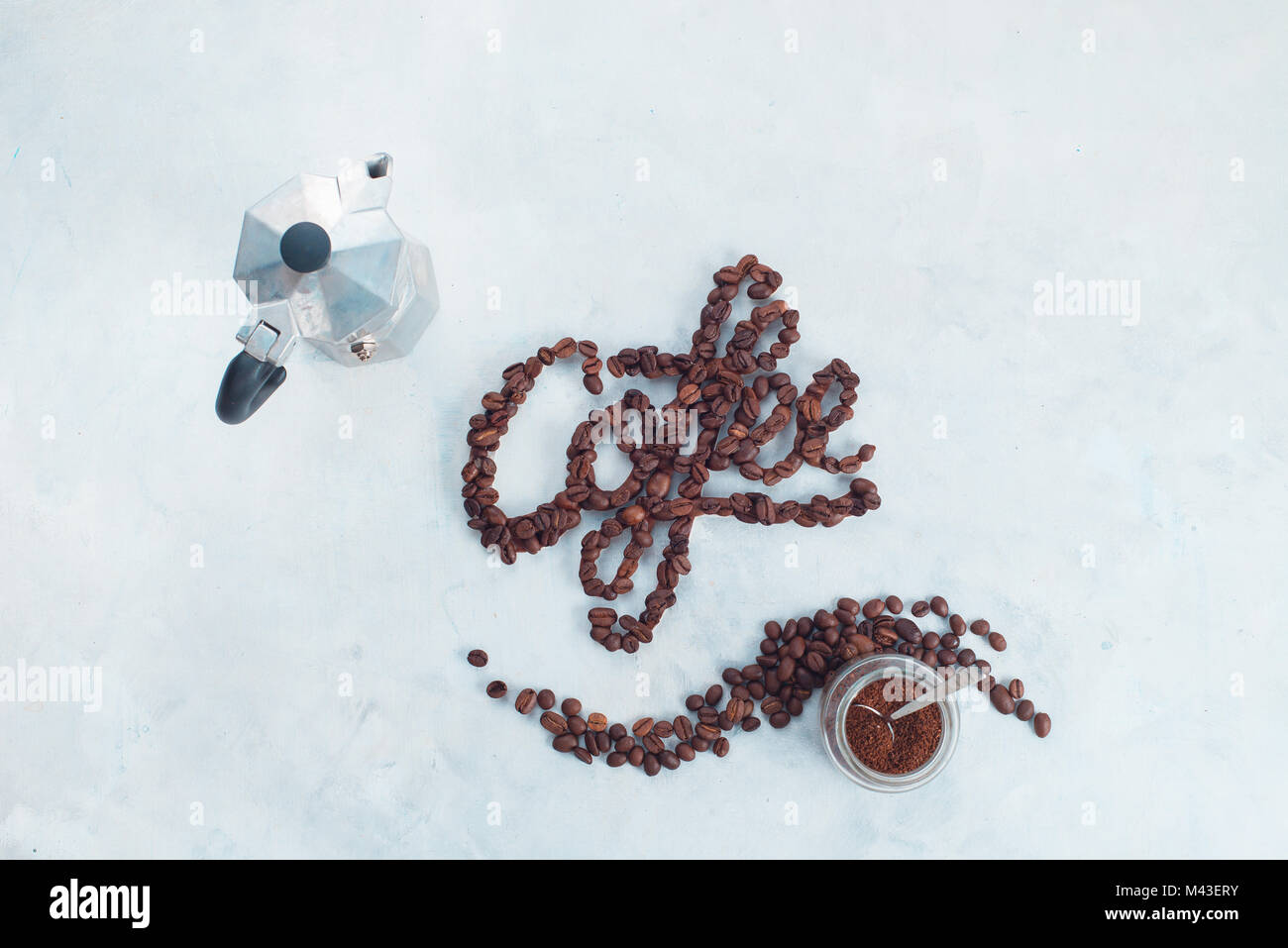 Word Coffee made with coffee beans. High key drink photography with Moka pot and food lettering. Creative top view - Stock Image