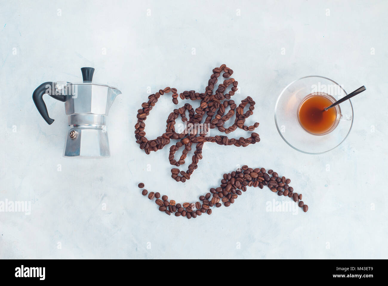Minimalist flat lay with word Coffee made with coffee beans. Brewing coffee in Moka pot concept. Creative top view - Stock Image