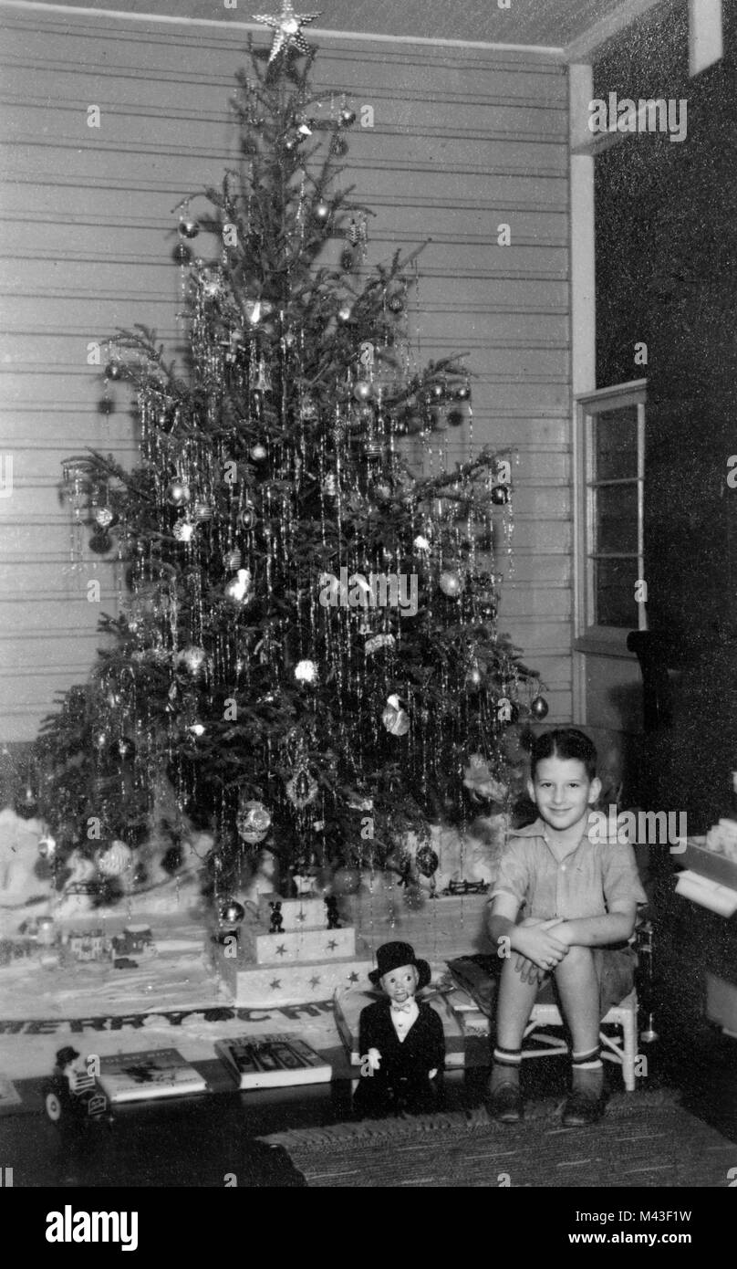 Young boy sits by the Christmas tree, ca. 1940. - Stock Image