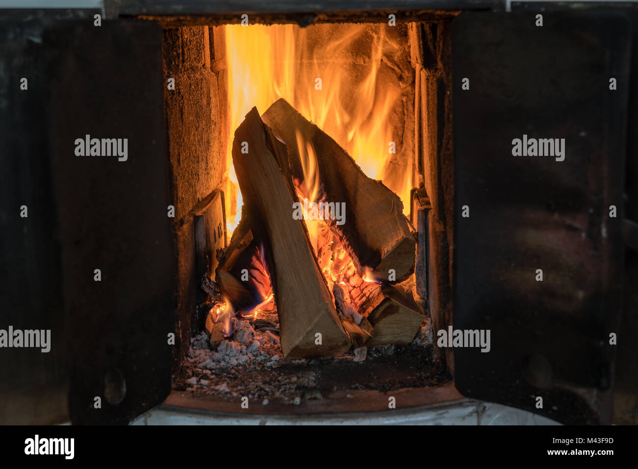 fire in a tiled stove with white tiles - Stock Image