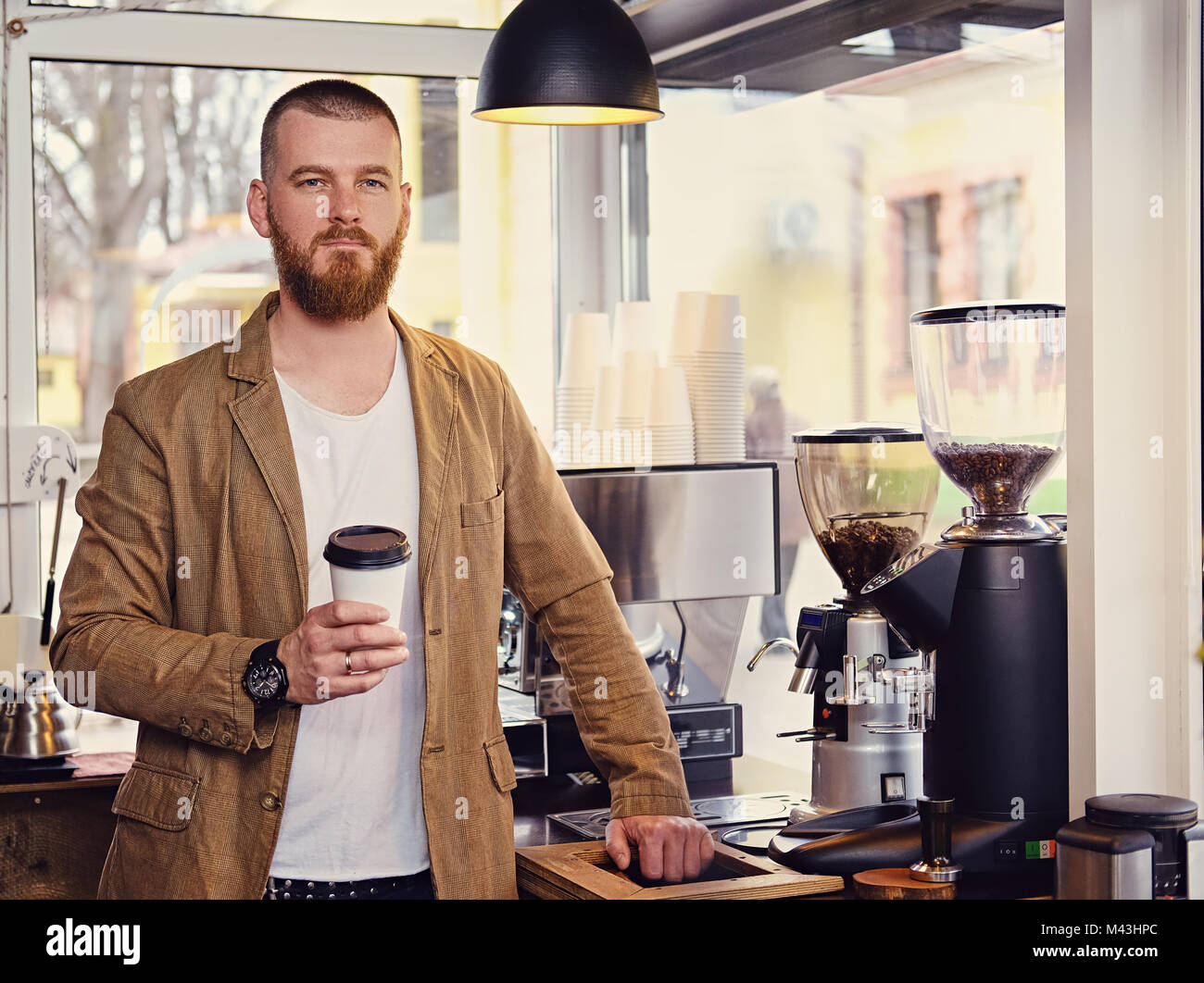 Redheads craft coffee seller in a small street cafe. - Stock Image