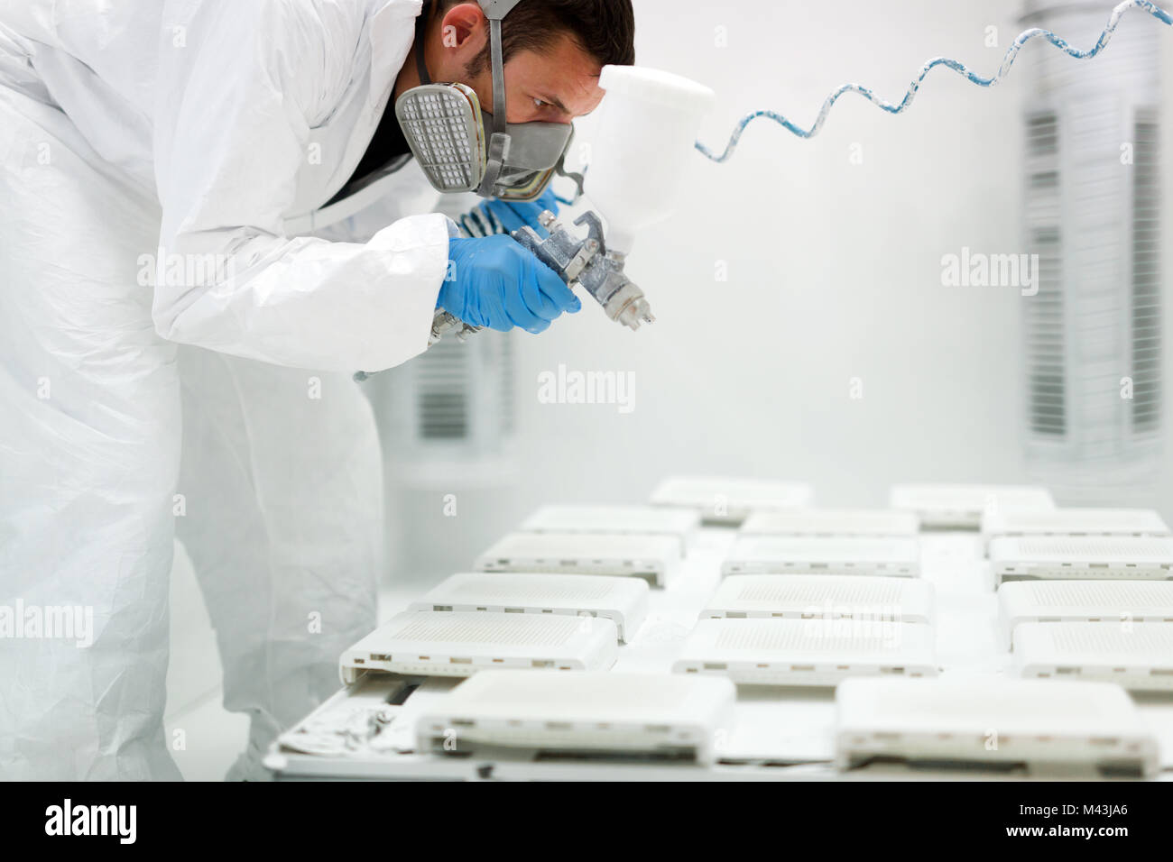 Painter using airbrush to paint wearing protective clothing - Stock Image