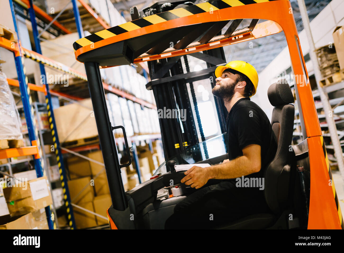 Warehouse worker doing logistics work with forklift loader - Stock Image