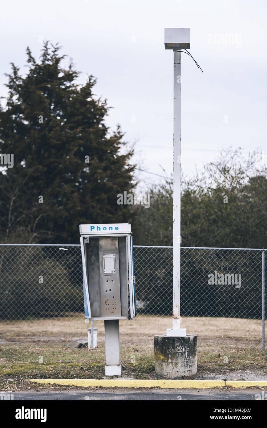 Abandoned payphone box next to a lamp post. Phone is missing. - Stock Image