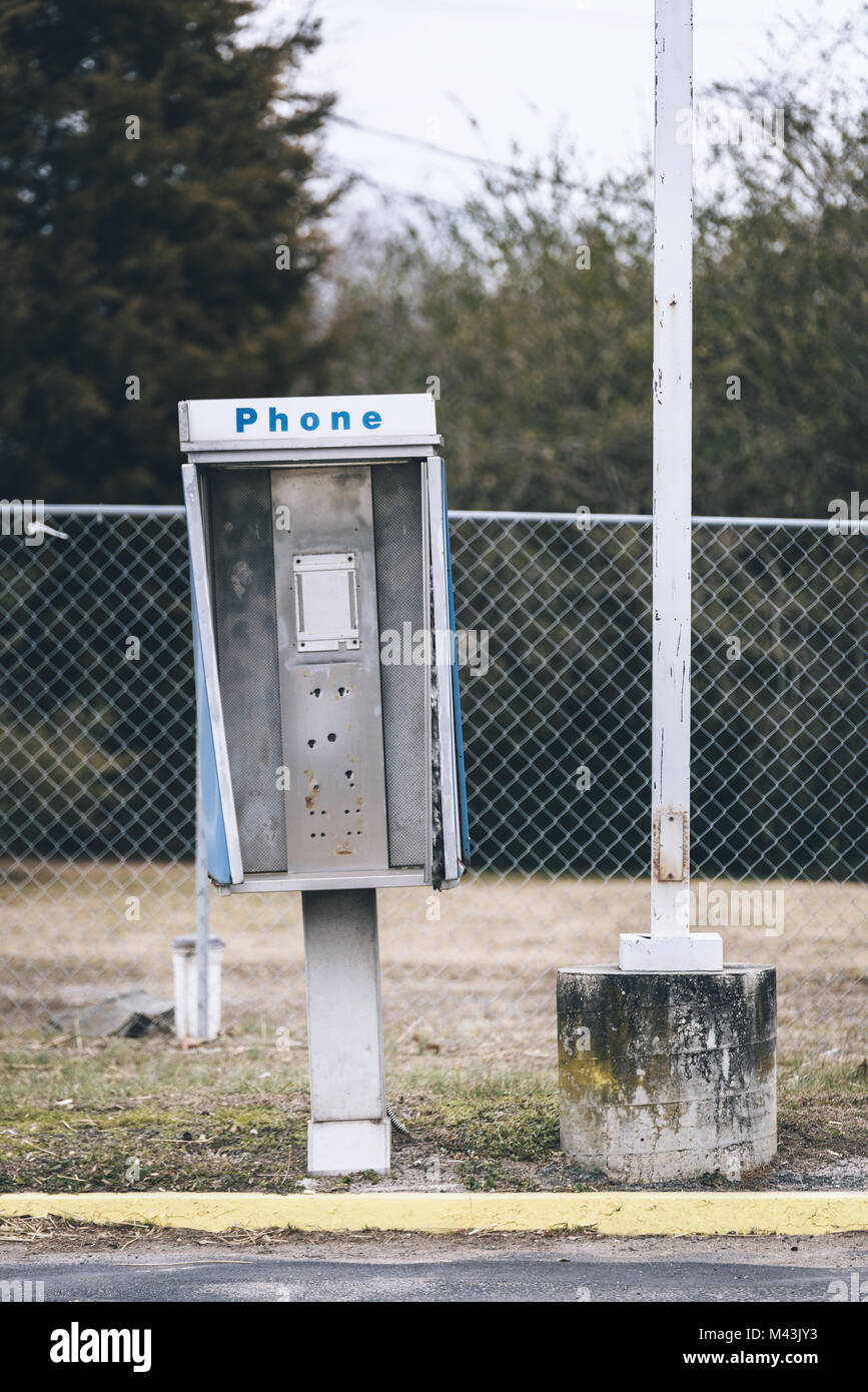 Abandoned payphone box. Phone is missing. - Stock Image