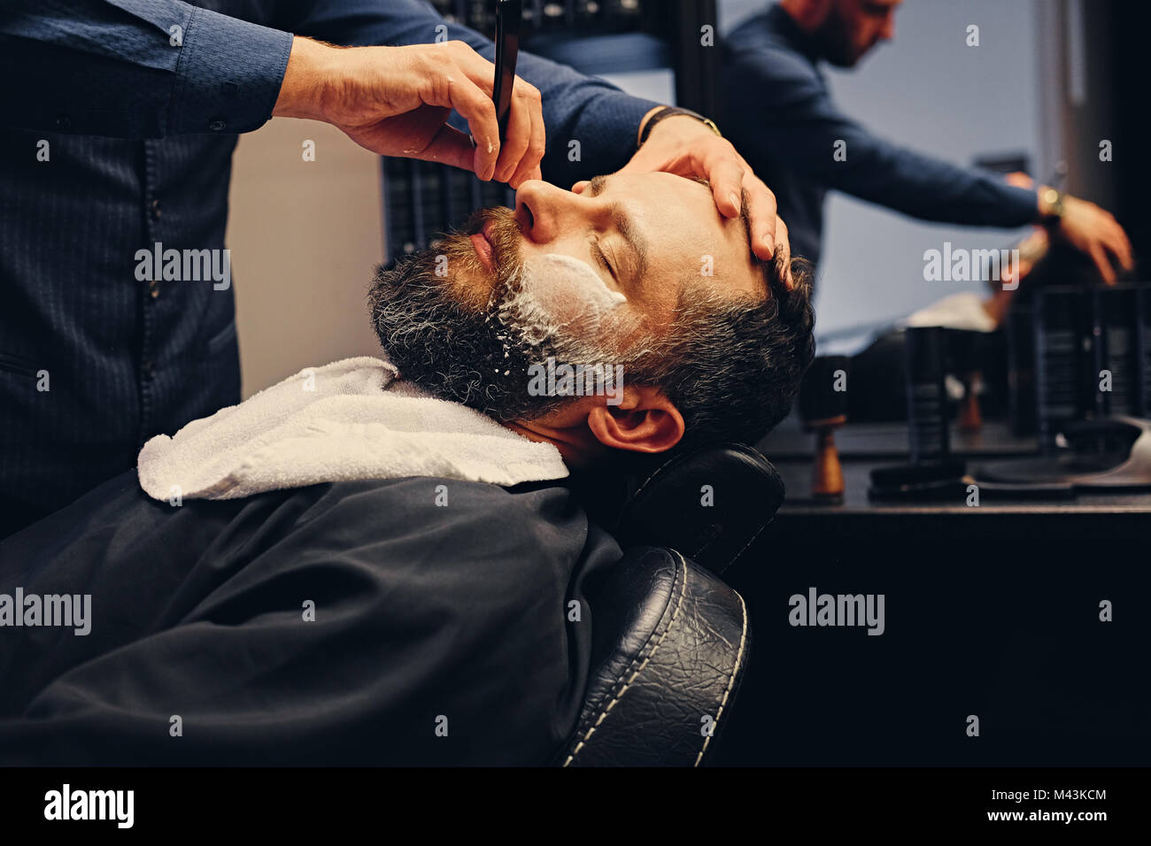 Barber shaving bearded male with a sharp razor. - Stock Image