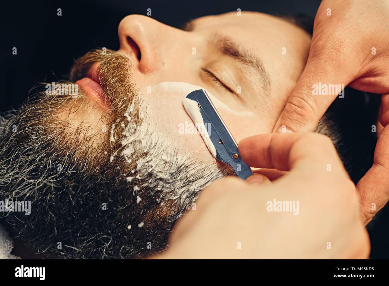 Barber shaving bearded male with a sharp razor. - Stock Image