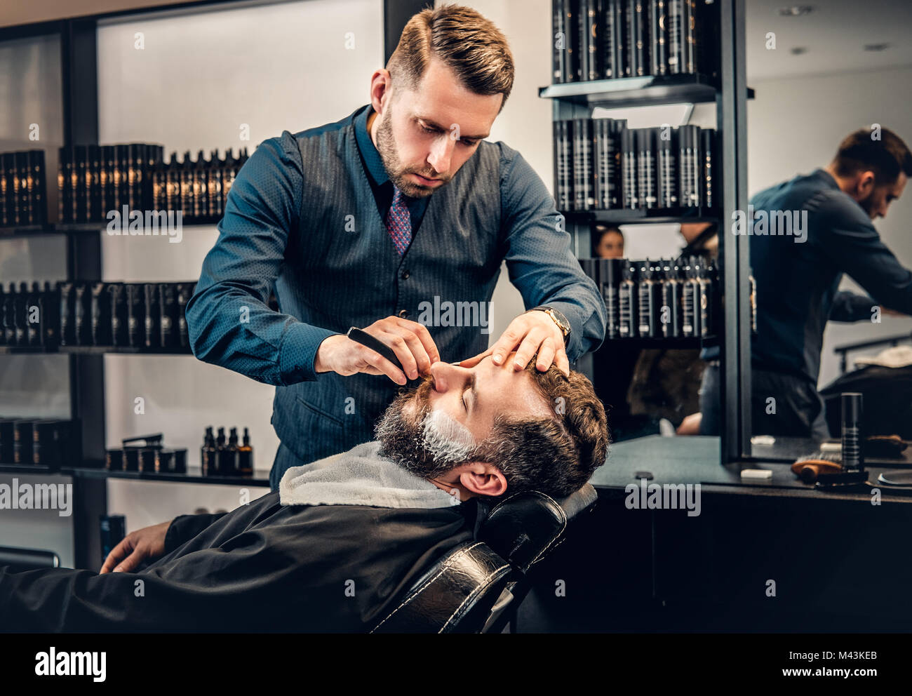 Stylish barber grooming a man's beard in a saloon. - Stock Image