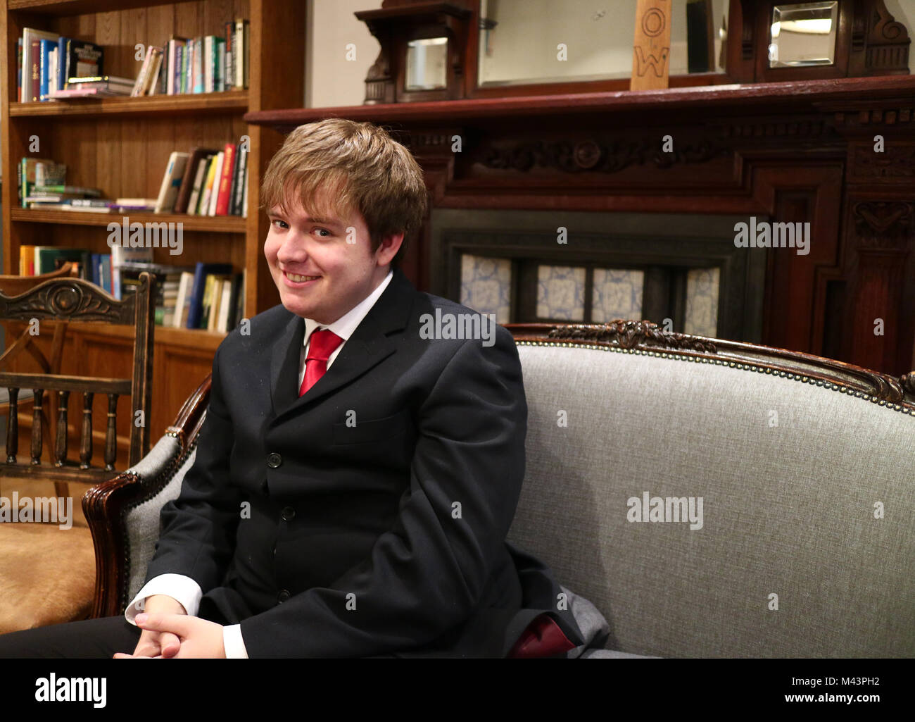 A young man smiling in a suit sat on a sofa taken from the side - Stock Image