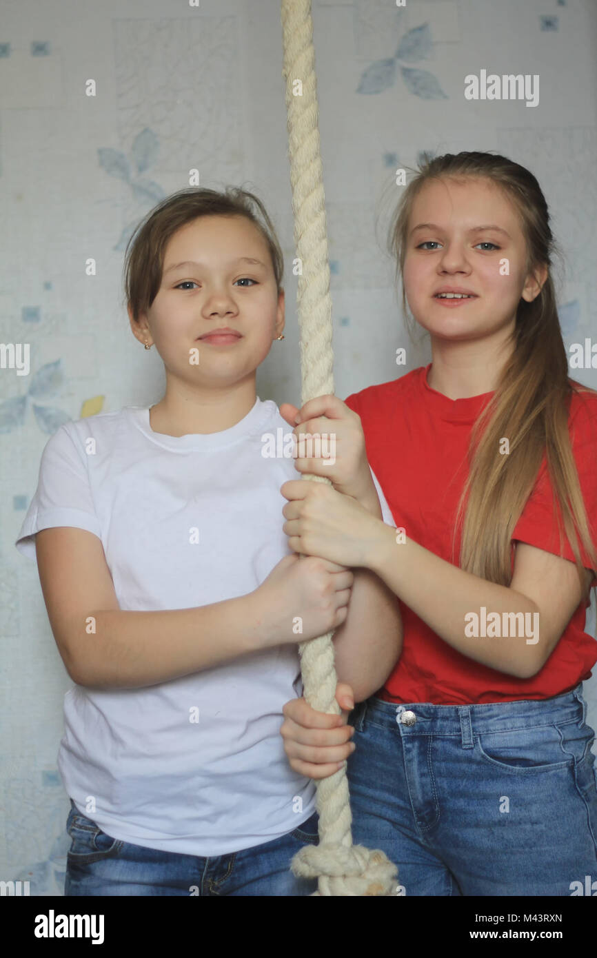 Portrait of two girlfriends or sistersat home posing near gymnastic rope - Stock Image