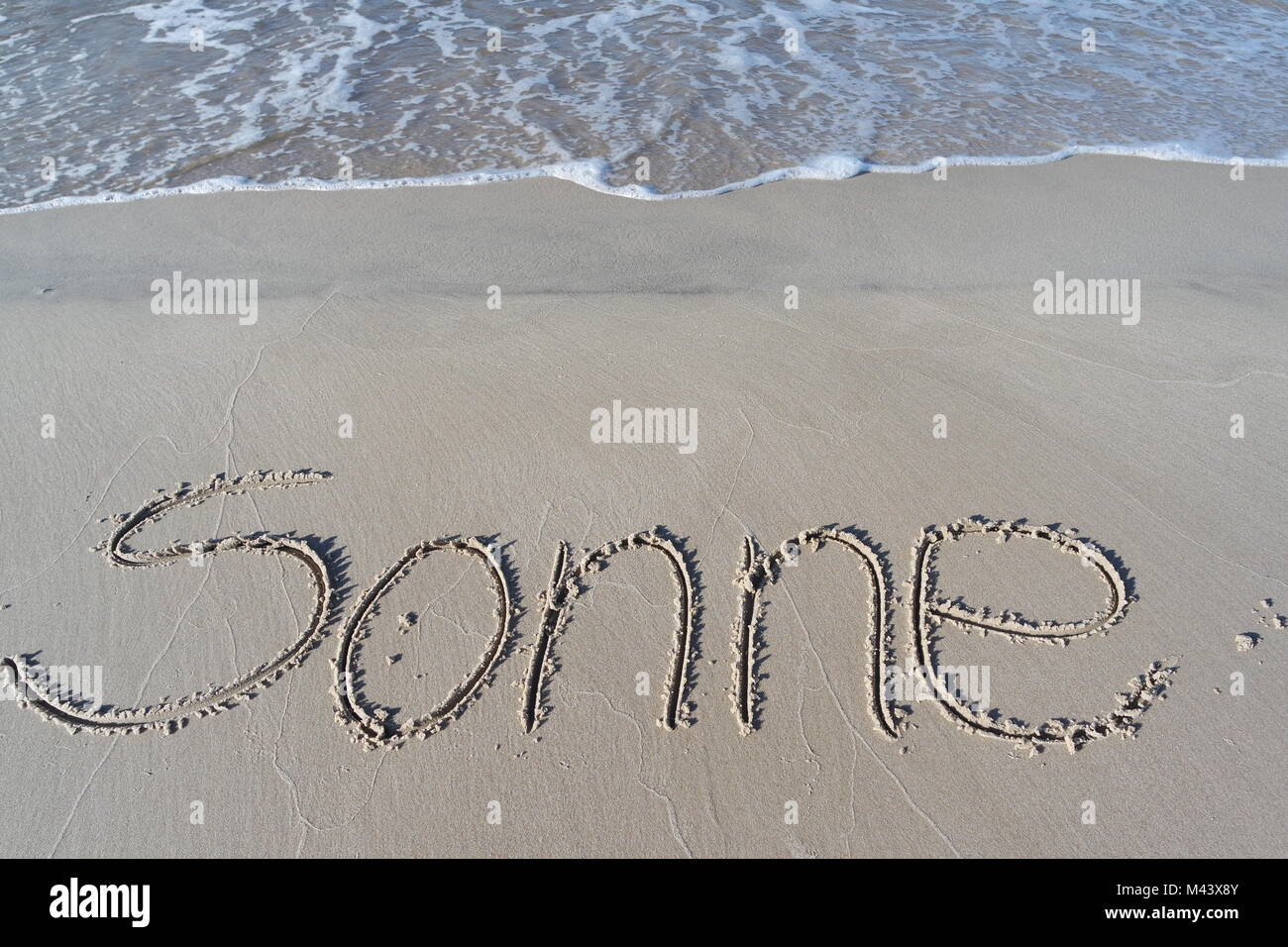 sun written in sand - Stock Image