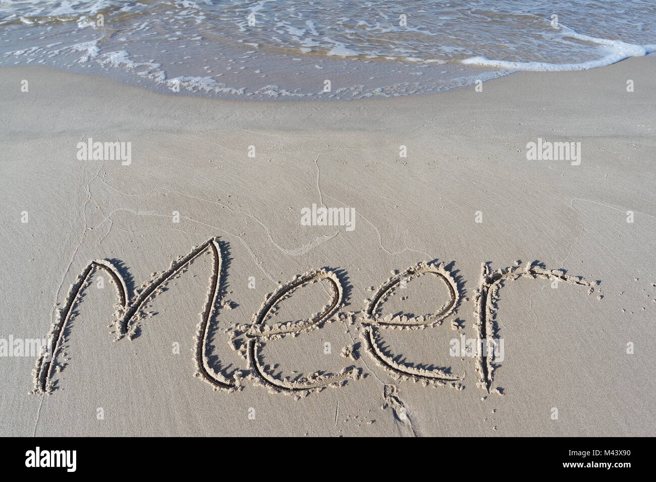 sea written in sand - Stock Image