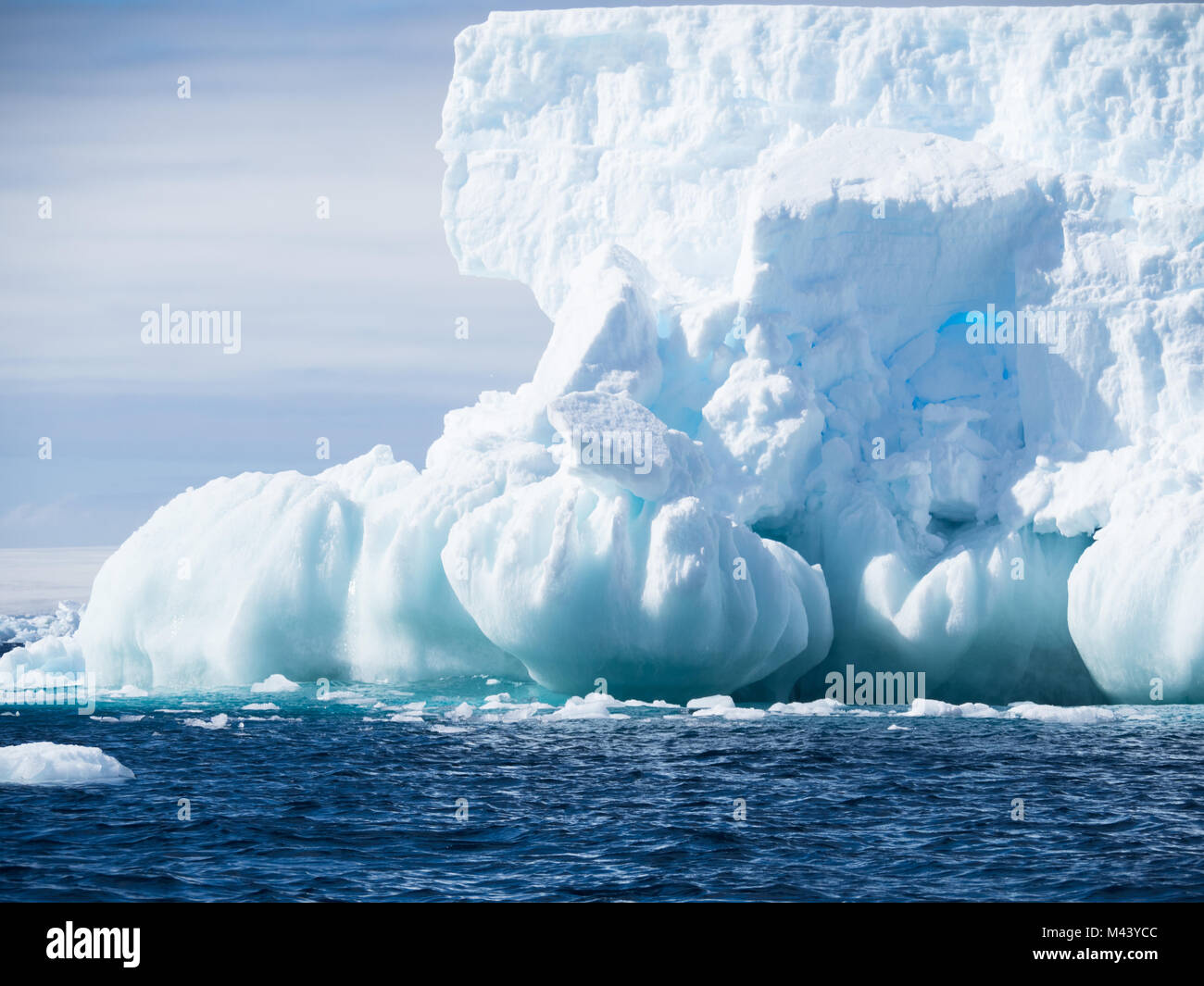 A large light blue iceberg with a foundation of spheres. The dark blue water of the Southern Ocean has small ripples. - Stock Image