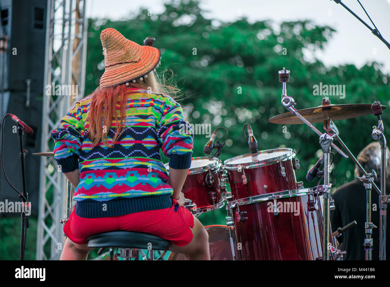 Shot of a girl with colorful clothes and orange hat playing drums on stage during music festival in summer. Band - Stock Image