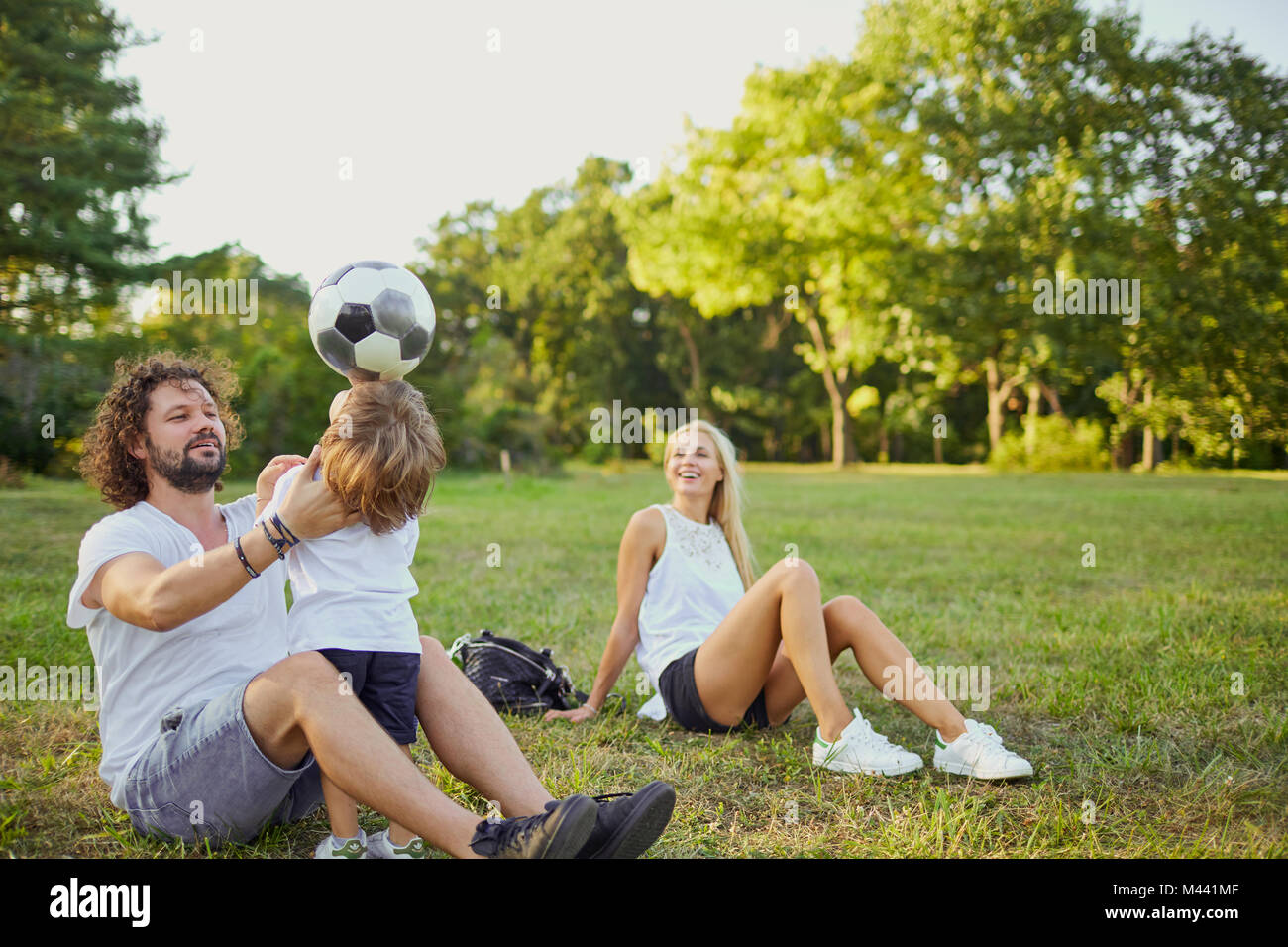 Family playing with a ball in the park.  - Stock Image