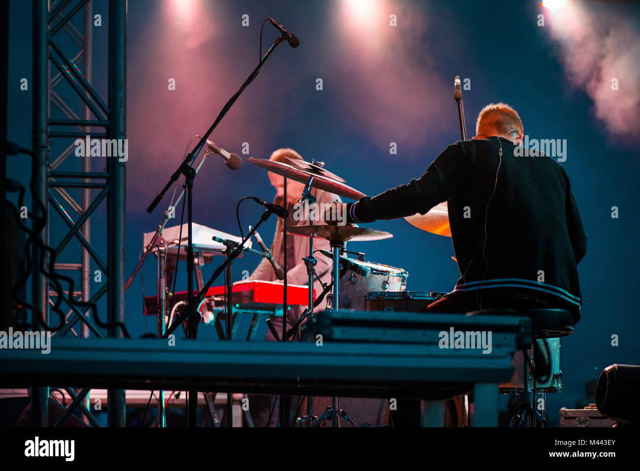 Artist playing on keyboard synthesizer piano keys, man playing drums on stage during music festival in summer. Band - Stock Image