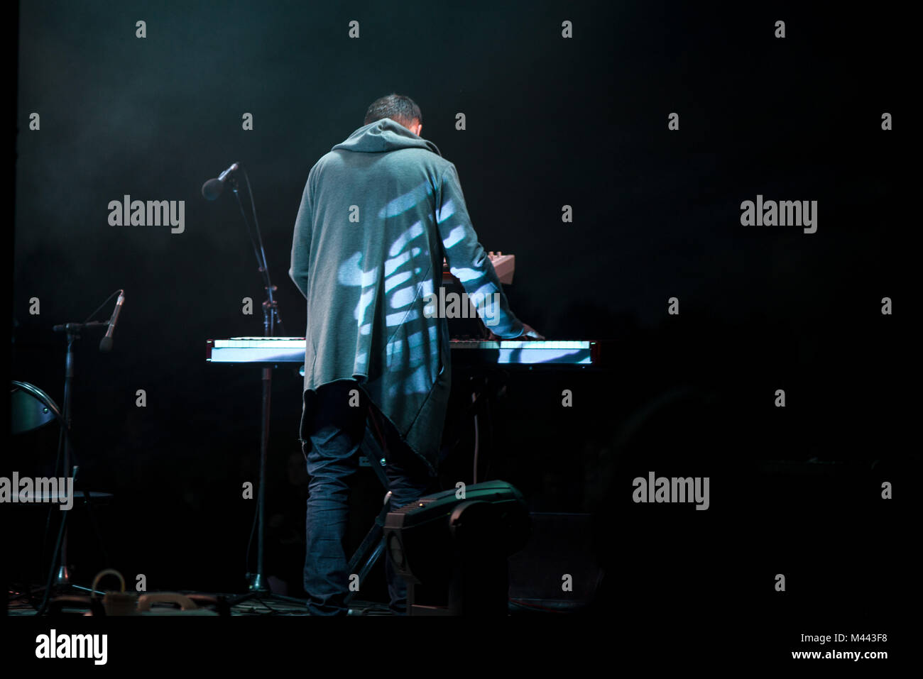 Male musician plays a musical instrument on the stage. Artist playing on the keyboard synthesizer piano keys. Live - Stock Image