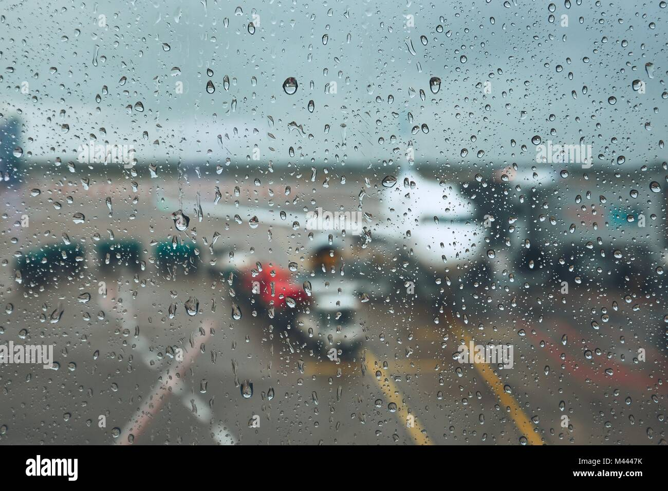 Storm at the airport. View of the airplane through rain drops. Themes weather and delay or canceled flight. - Stock Image