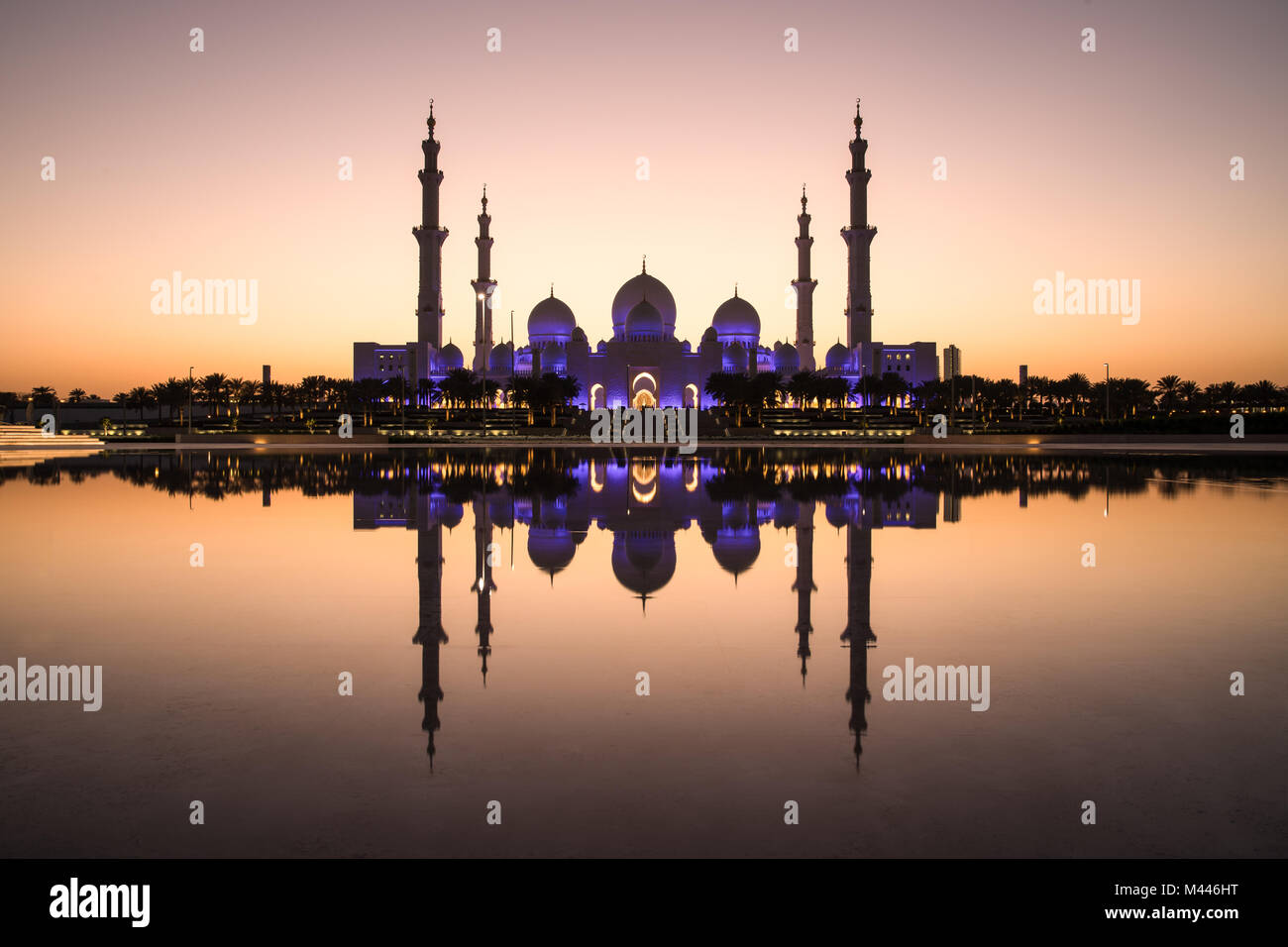 Sheikh Zayed Grand Mosque and it's perfect reflection in a water pool during dusk after sunset. Abu Dhabi, UAE. - Stock Image