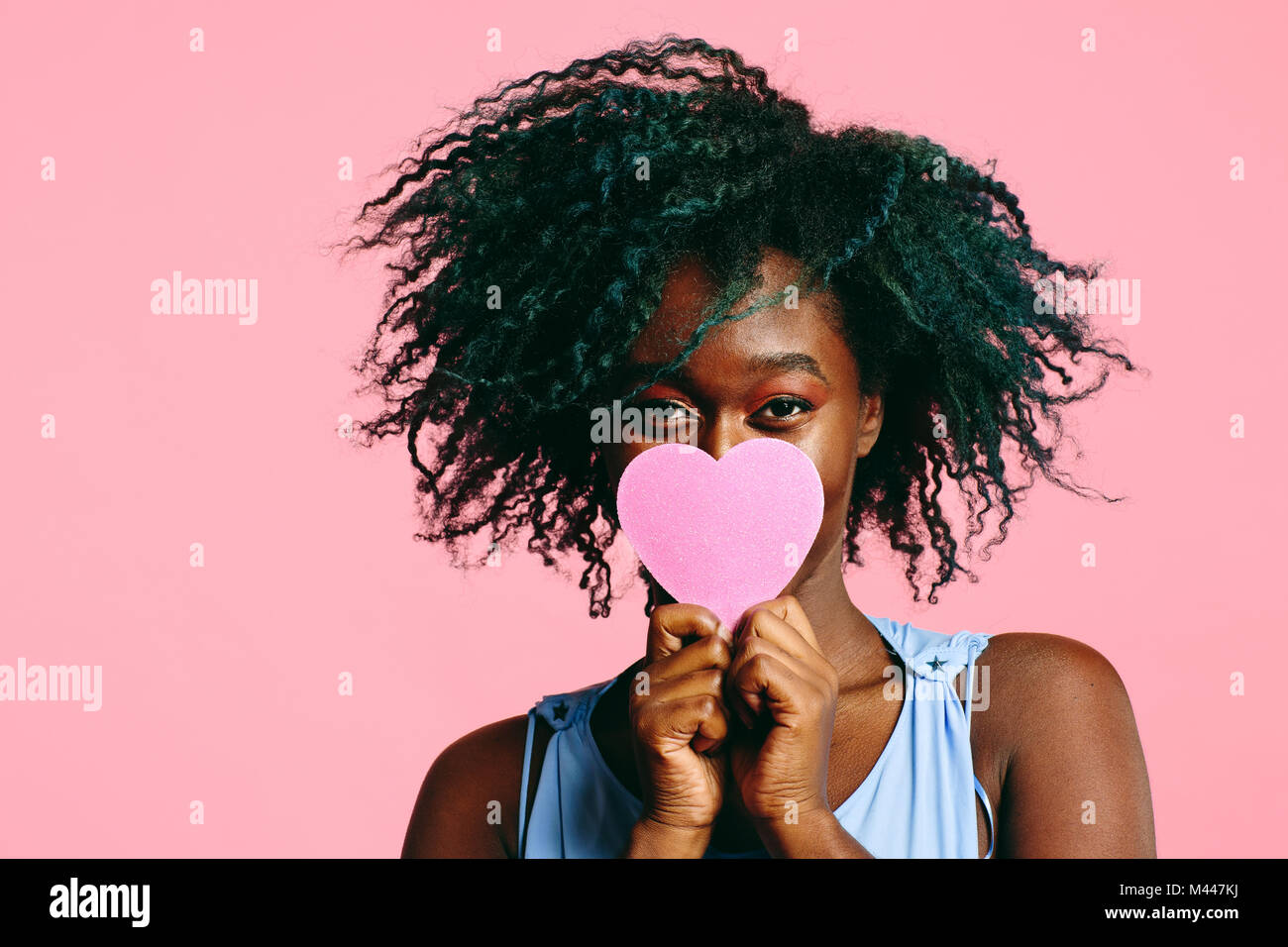 Girl with blueish black curly hair holding a pink heart in front of her face - Stock Image