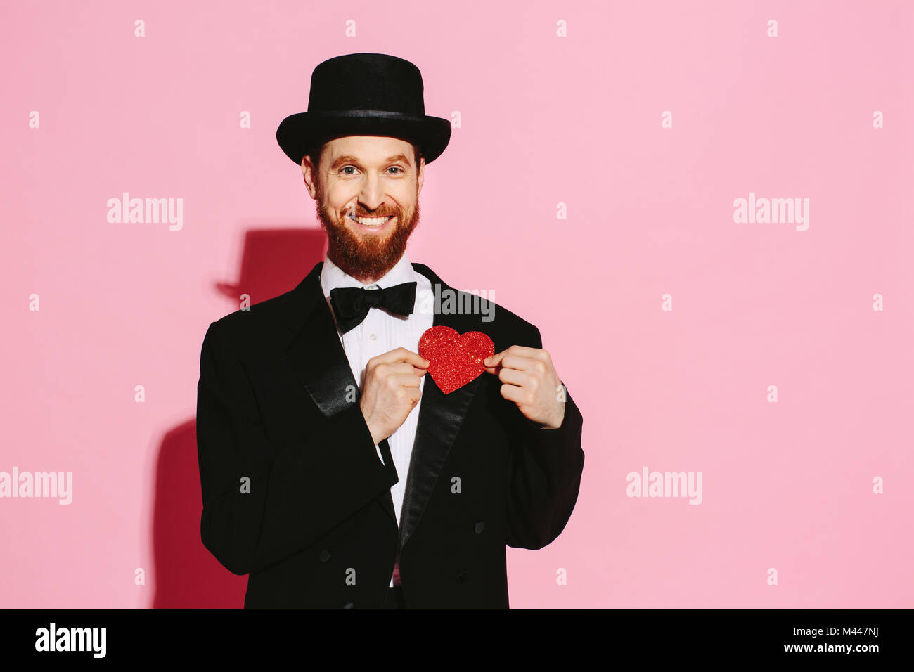 Smiling man in a tuxedo and top hat holding a red heart - Stock Image