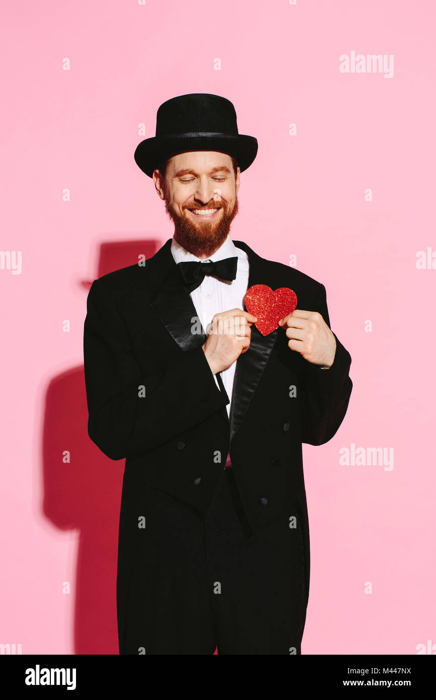 Smiling man with closed eyes in suit and top hat holding red heart on his chest - Stock Image