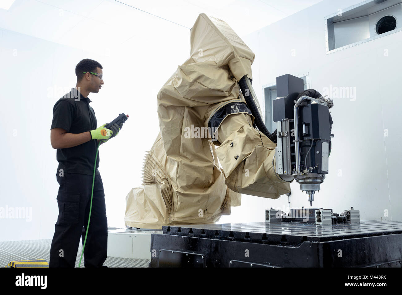Apprentice robotics engineer with robot in robotics research facility - Stock Image