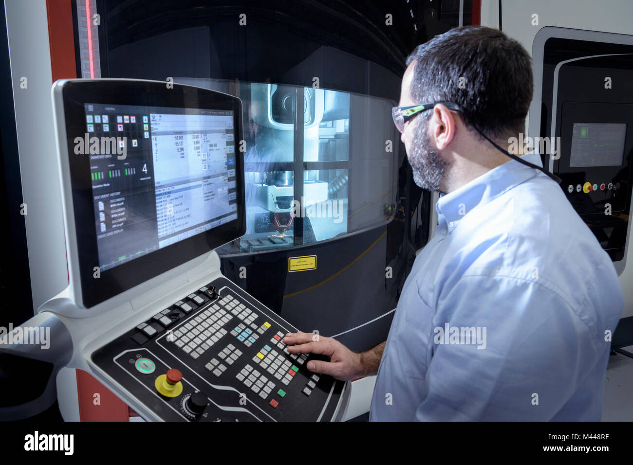 Operator with stainless steel 3D printer in robotics research facility - Stock Image