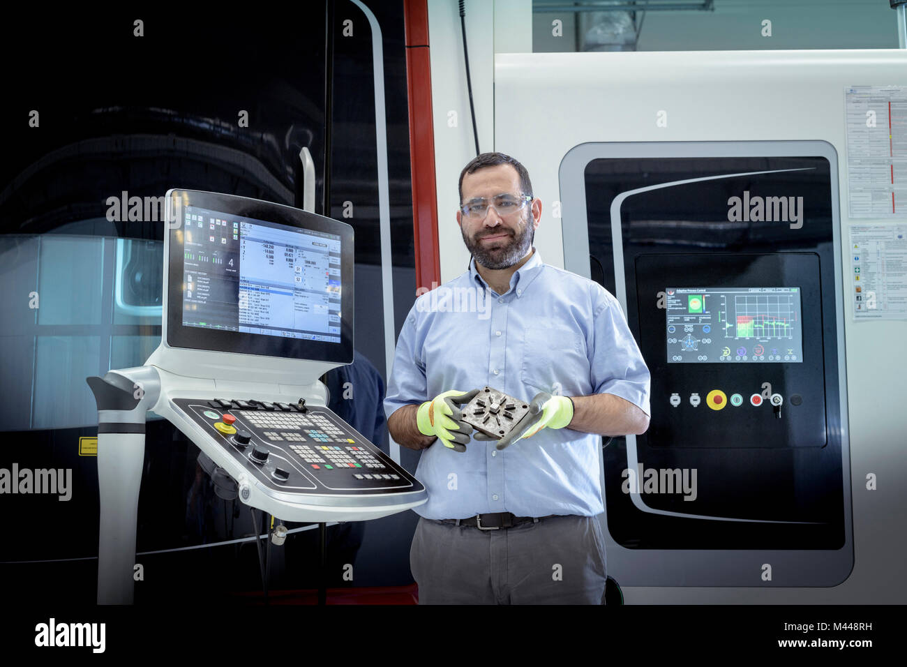 Portrait of operator with stainless steel 3D printer in robotics research facility - Stock Image