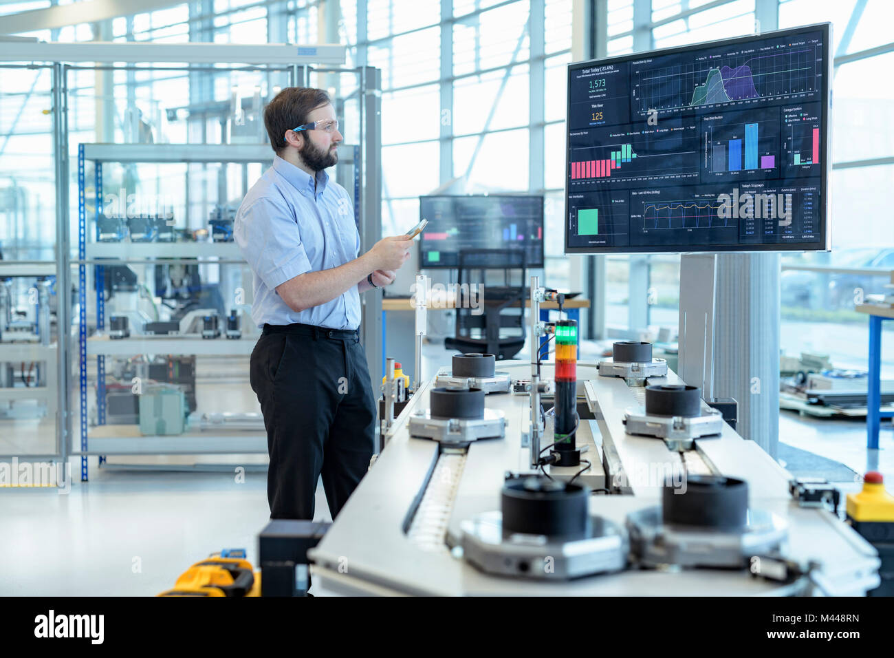 Engineer testing a robotic production simulator in robotics research facility - Stock Image