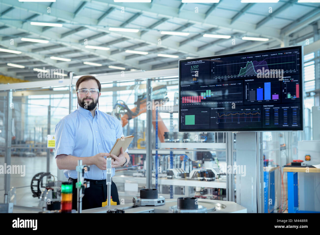 Portrait of robot engineer in robotics research facility - Stock Image