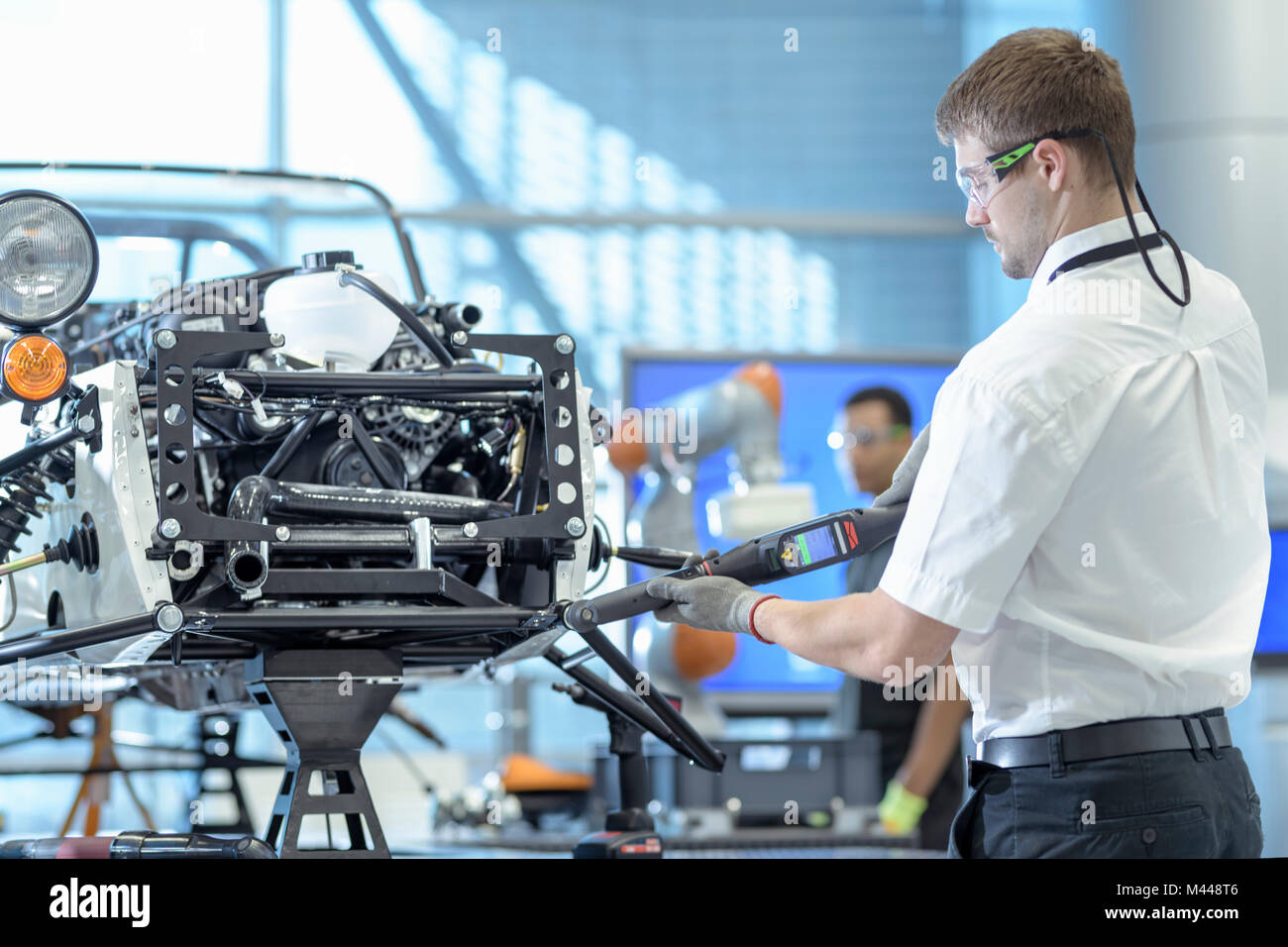 Engineer using computerised tools to assemble car in robotics research facility - Stock Image