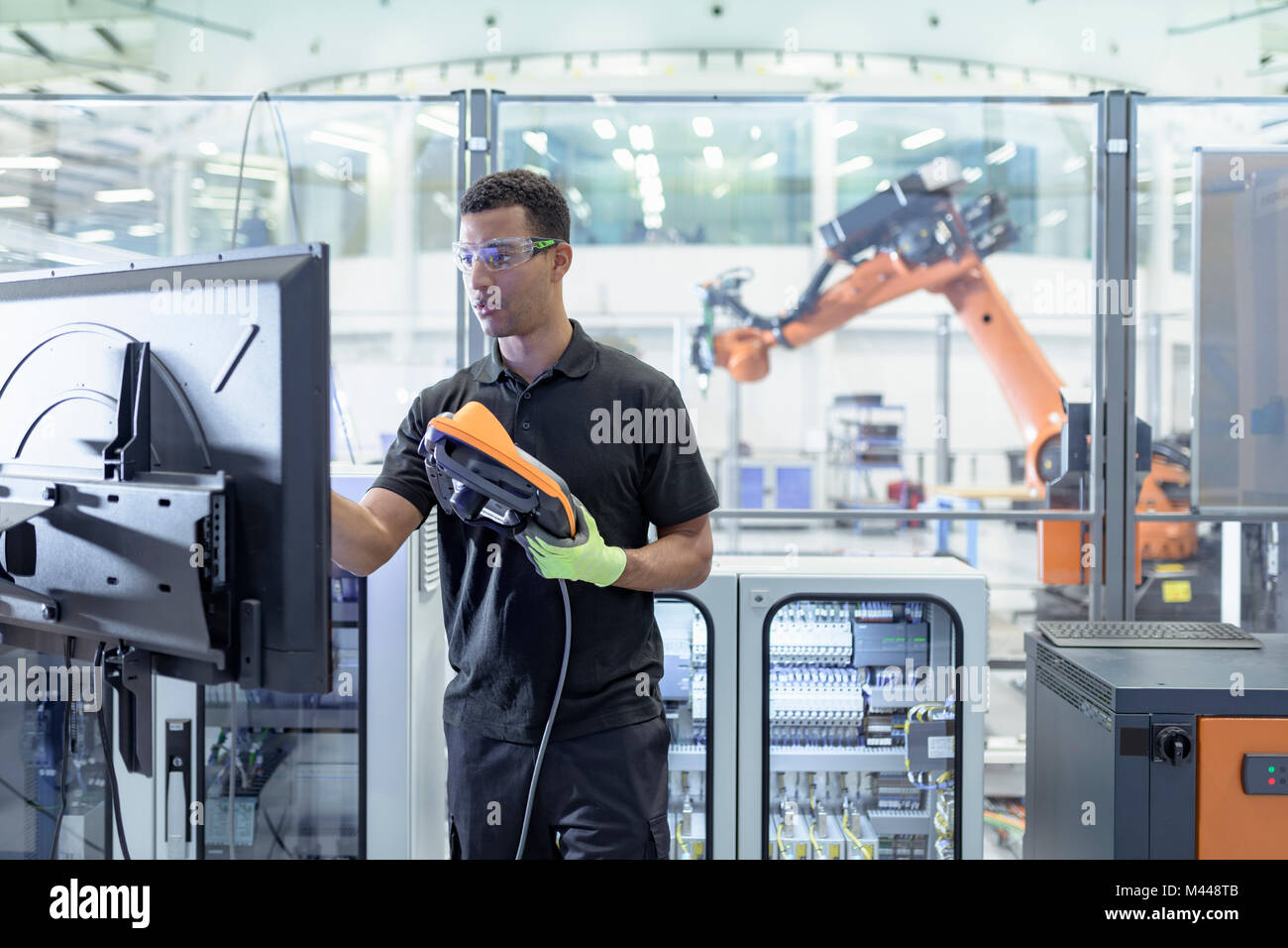 Engineer programming robot in robotics research facility Stock Photo