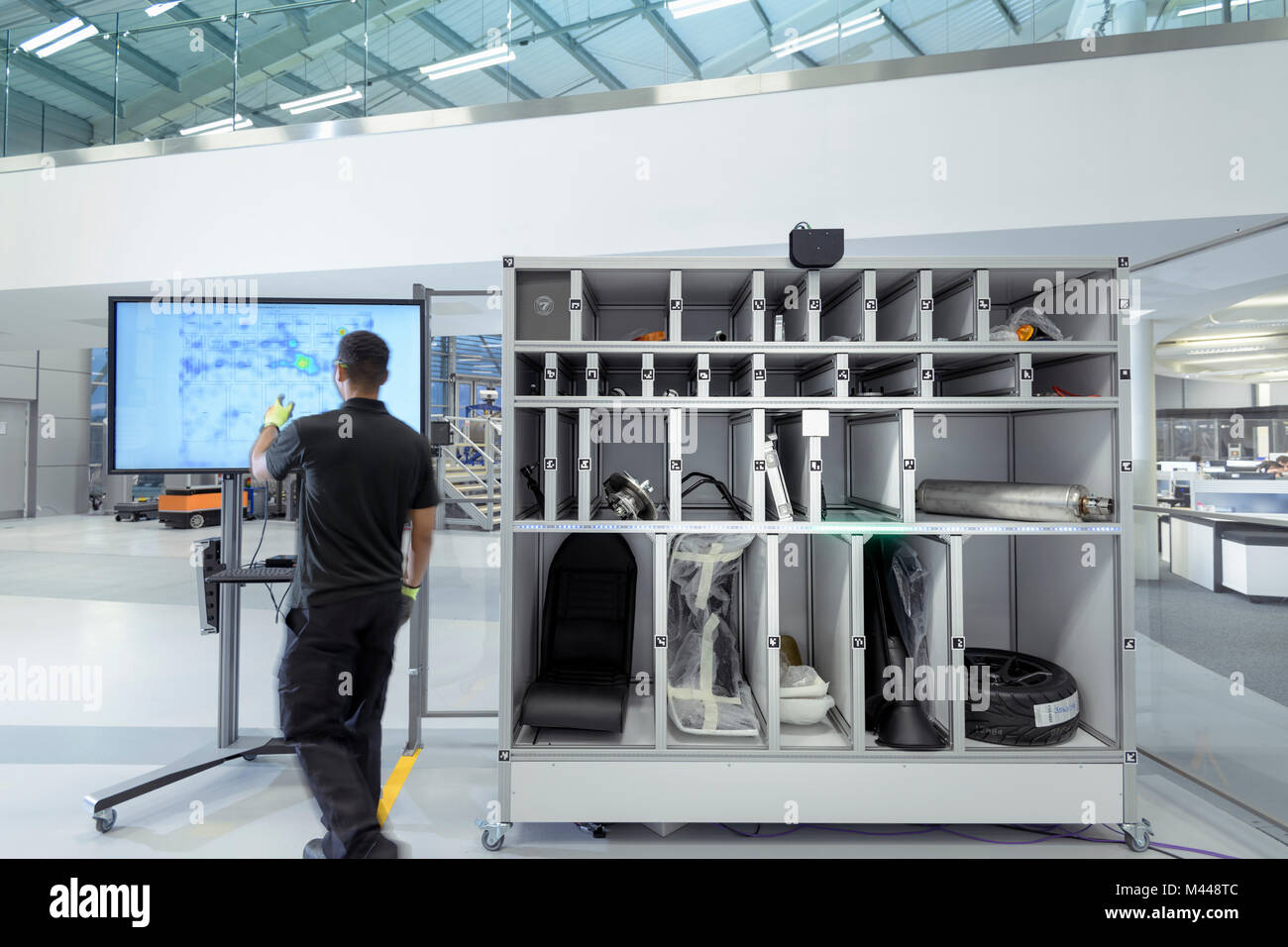 Engineer using artificial intelligence aid to pick parts for product assembly in robotics research facility Stock Photo
