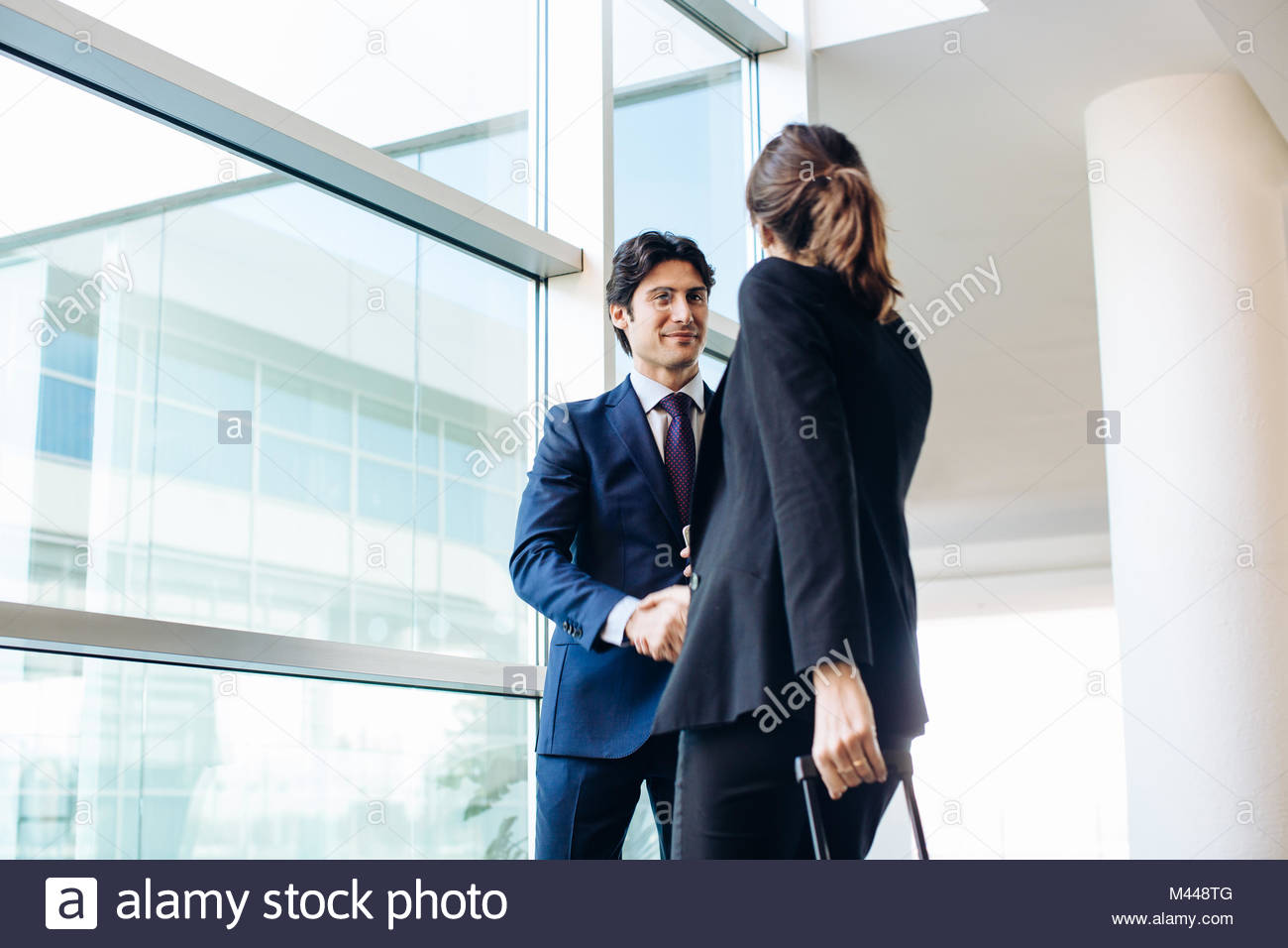 Businessman and businesswoman with wheeled luggage in hotel building - Stock Image