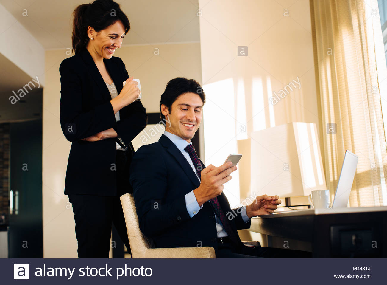 Businessman and businesswoman sharing text message in hotel room Stock Photo
