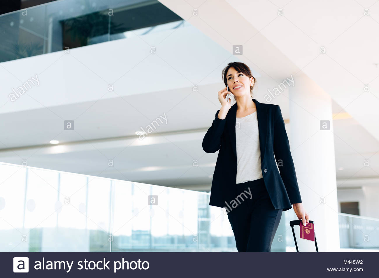 Businesswoman with wheeled luggage in hotel building - Stock Image