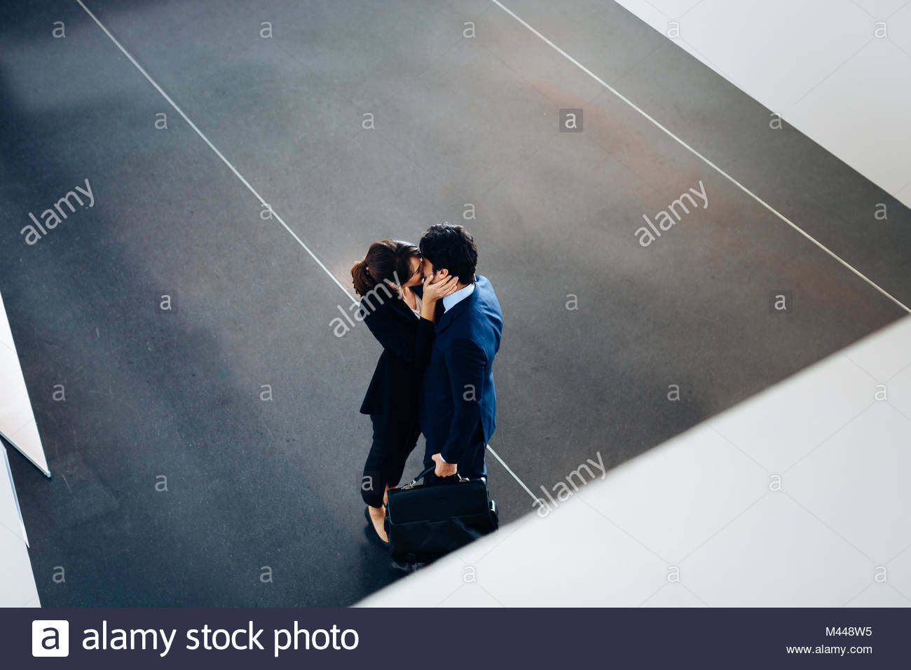 Couple in business suits kissing - Stock Image