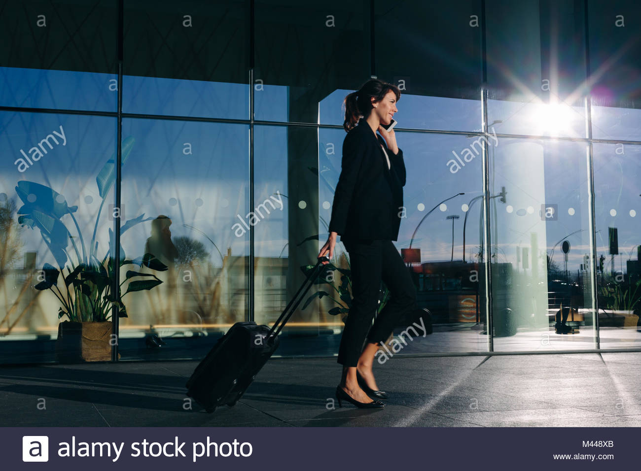 Businesswoman with wheeled luggage passing glass building, Malpensa, Milan - Stock Image
